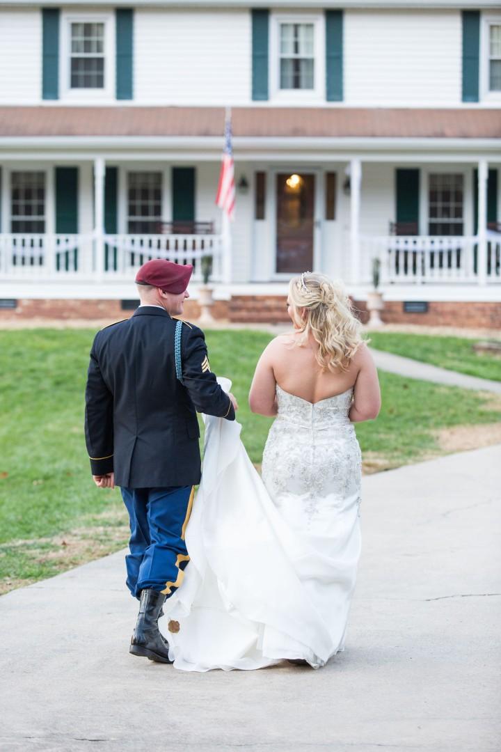 Groom holding wedding dress for bride
